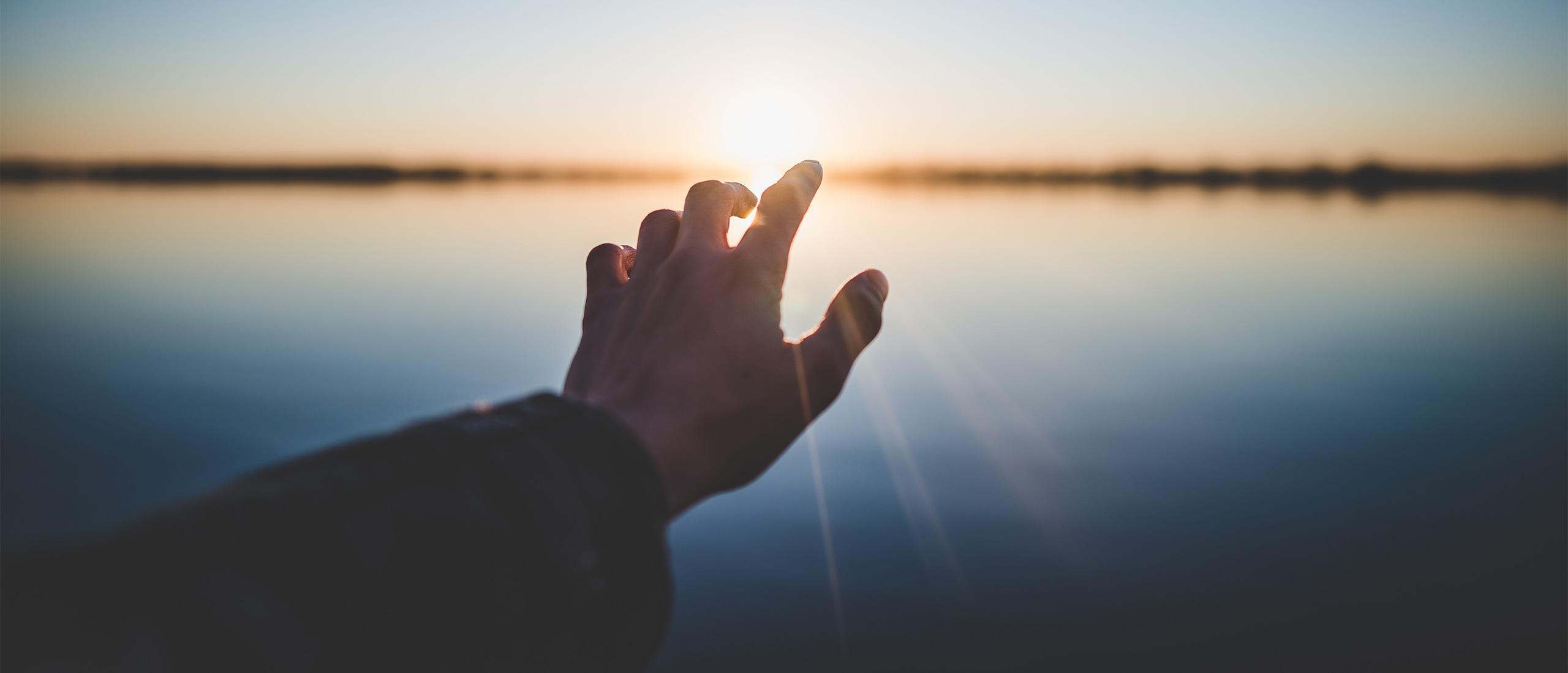 """Banner """"Kontakt"""": Ausgestreckte Hand, zeigt auf aufgehende Sonne über Meeres-Hoirzont"""
